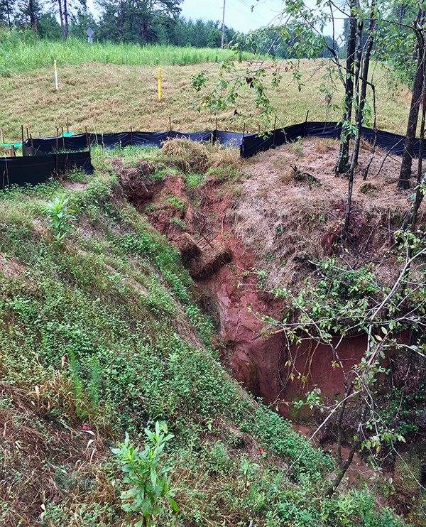 Deep gully forming beside Dominion's new high pressure natural gas pipeline in Spartanburg County. The yellow pole is the pipeline's location.